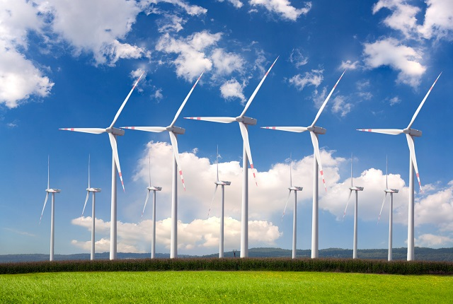 A large group of wind turbines making up a wind farm on land.