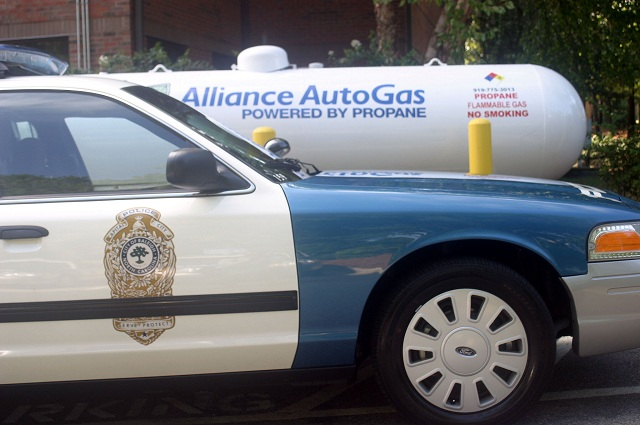 An autogas cruiser from the Raleigh, N.C., Police Department in front of an Alliance AutoGas fuel tank.