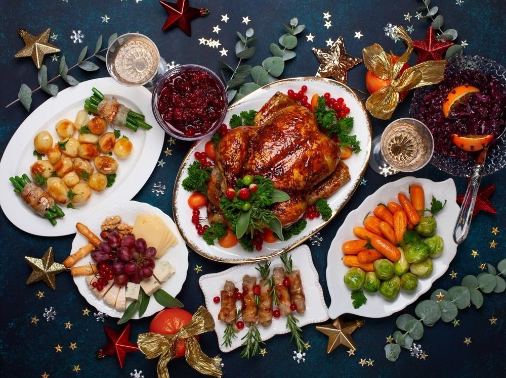 Concept of Christmas or New Year dinner with roasted chicken and various vegetables dishes.